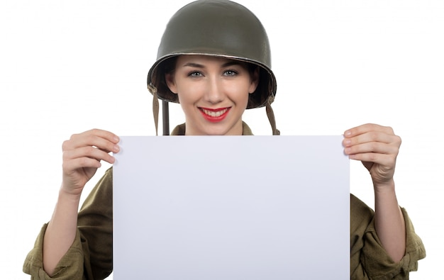 Young woman dressed in wwii military uniform with helmet showing empty blank signboard with copyspace