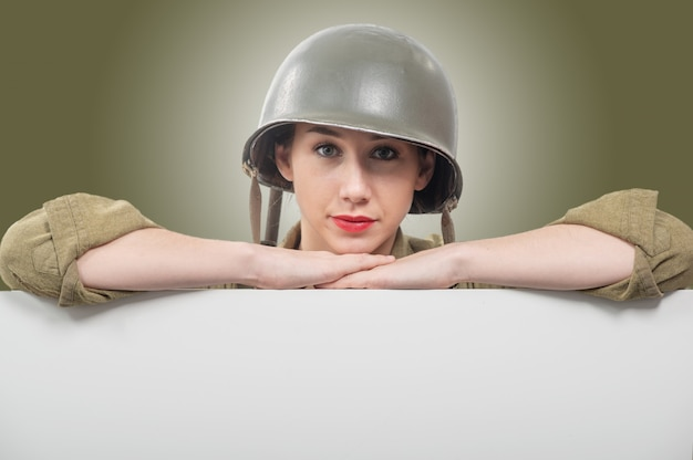 Young woman dressed in wwii military us uniform with helmet showing empty blank signboard