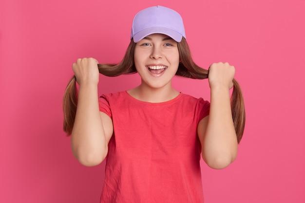 Молодая женщина одевается в красную футболку и бейсболку, позирует на розовой стене, держит волосы в руках, как хочет, делает хвостики, выглядит взволнованной