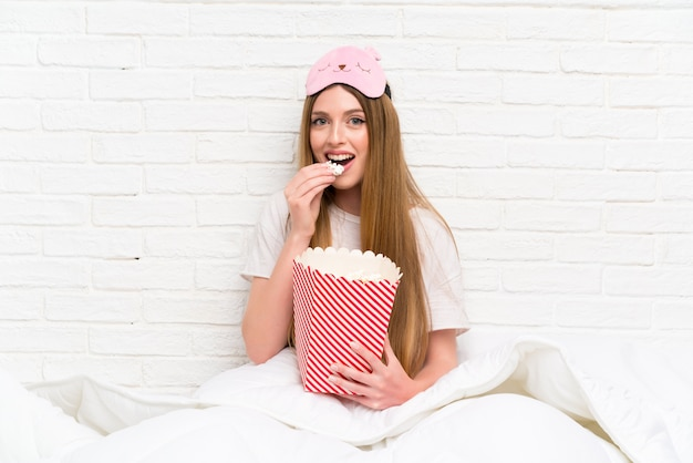 Young woman in dressing gown in bed holding popcorns