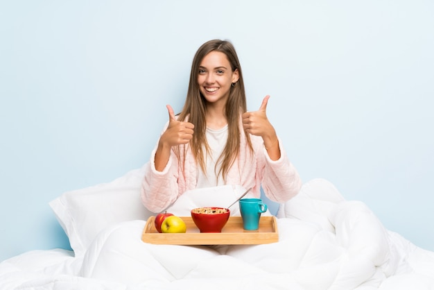 Young woman in dressing gown with breakfast giving a thumbs up gesture