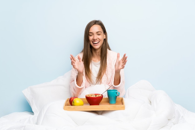 Young woman in dressing gown with breakfast laughing