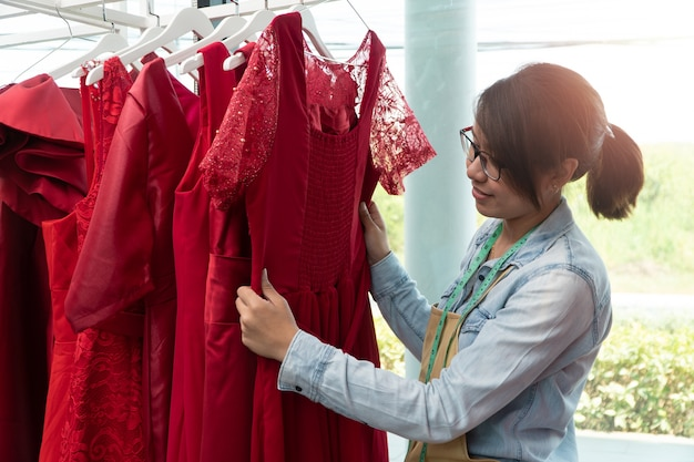 Young woman dressmaker checking the dresses