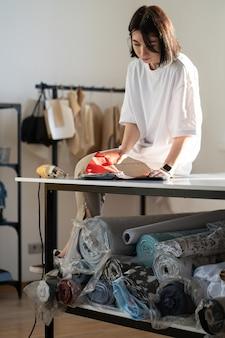 젊은 여성 양장점은 디자인 스튜디오 또는 아틀리에에서 옷을 바느질하기 위해 천 카탈로그의 직물을 선택합니다.