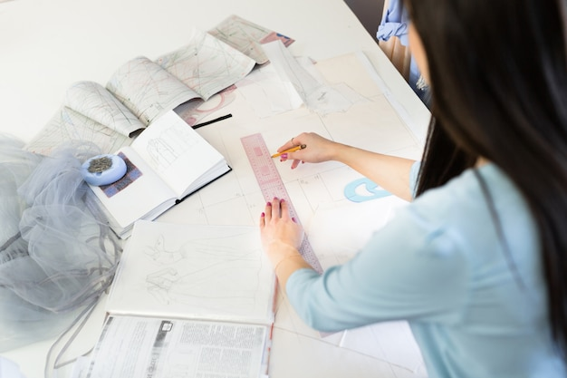 Young woman dressmaker designing clothes on tracing paper with pattern