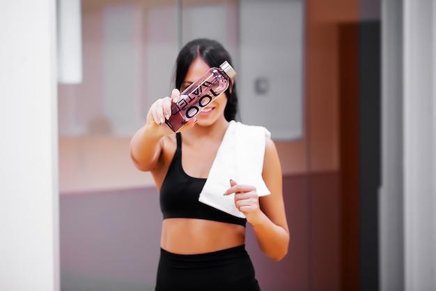 若い女性はフィットネスジムできれいな水を飲む