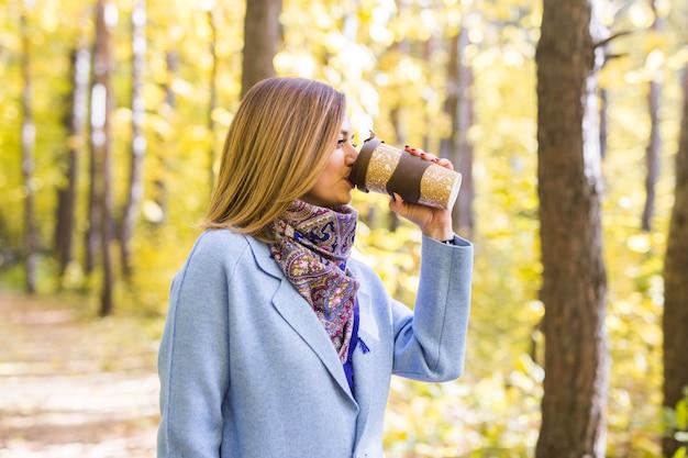 若い女性は秋の公園でコーヒーを飲む