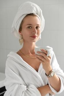 젊은 여자 화장실에서 커피를 마신다. 피부 관리 루틴. 느린 생활 중지 서두르고 즐기는 생활 개념
