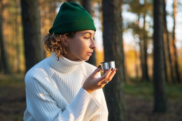 젊은 여성은 가을 숲에서 산책하는 보온병에서 뜨거운 차나 커피를 마시고 도시 밖의 자연을 즐깁니다.