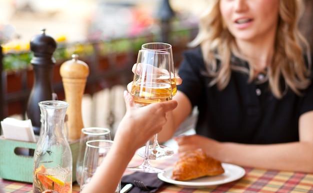 친구와 함께 카페 테라스에서 화이트 와인을 마시는 젊은 여자