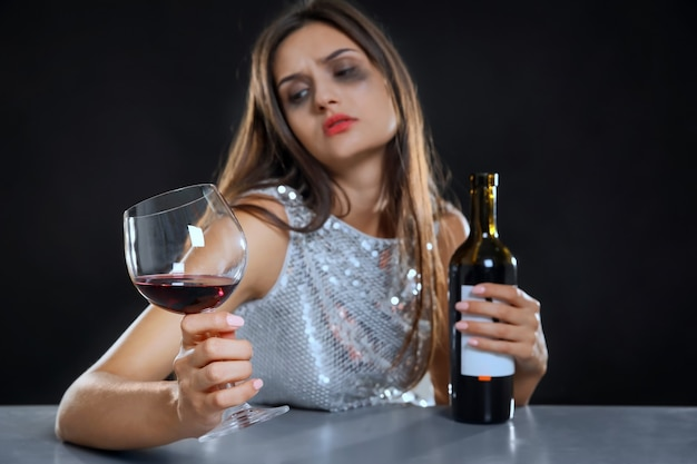 Young woman drinking alcohol at table against black