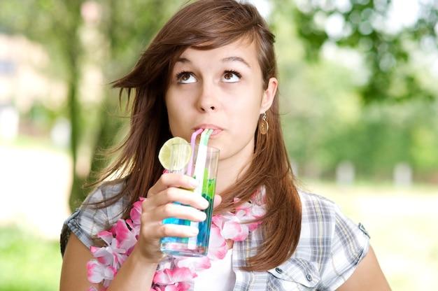 블루 큐 라 소 칵테일을 마시는 젊은 여자