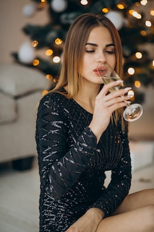 Giovane donna che beve champagne dall'albero di natale