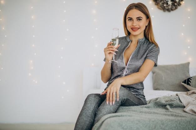 Молодая женщина пьет шампанское на рождество