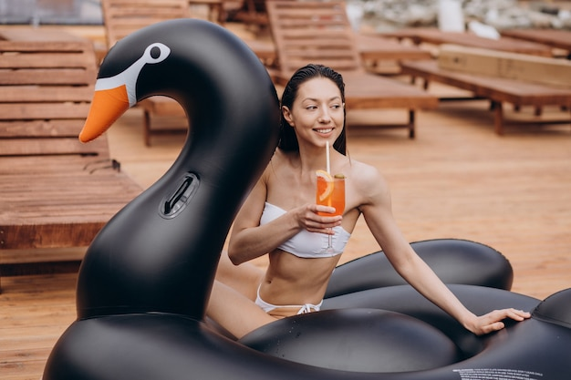 Giovane donna che beve cocktail a bordo piscina