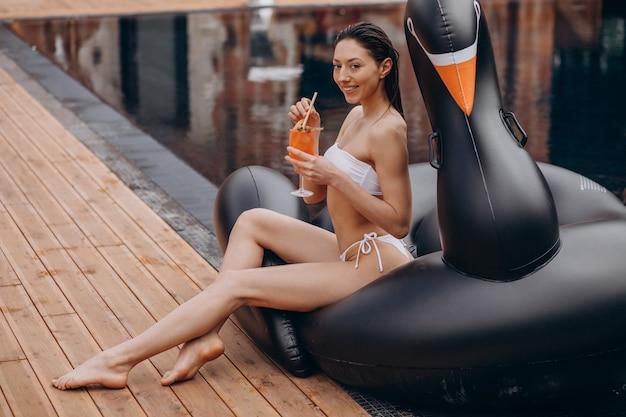 Молодая женщина пьет коктейль у бассейна