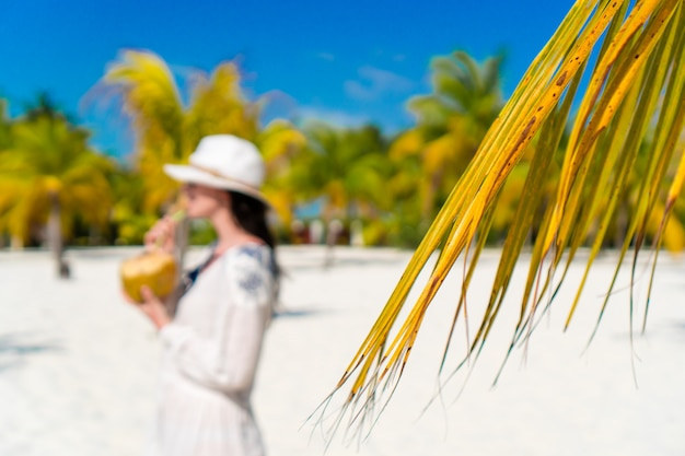 Young woman drinking coconut milk on hot day on the beach. closeup palm leaves