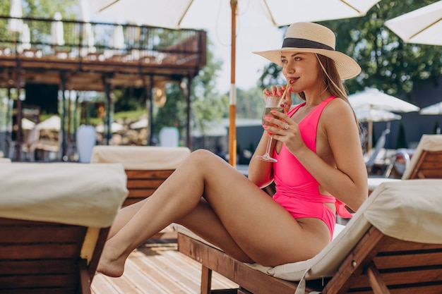 Young woman drinking coctail and lying on sunbed
