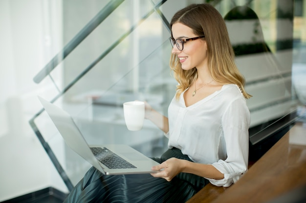 Young woman drinking coffe and working on laptop in office