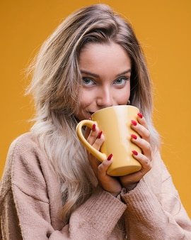 Young woman drinking coffee against yellow background