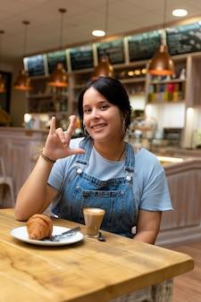 コーヒーを飲み、愛のしるしを作る若い女性