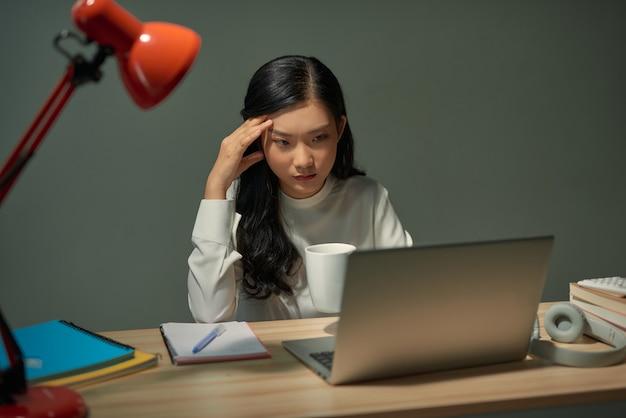 コーヒーを飲み、コンピューター画面で何かを読んでいる若い女性