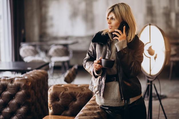 Молодая женщина пьет кофе и разговаривает по телефону в кафе