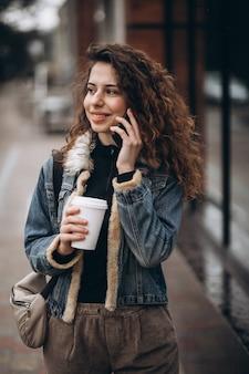 コーヒーを飲みながら携帯電話を使用して若い女性