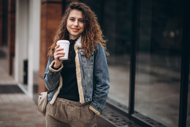 Молодая женщина, пить кофе и с помощью телефона