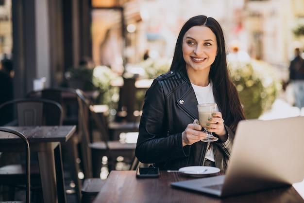 Молодая женщина пьет кофе и работает на ноутбуке в кафе