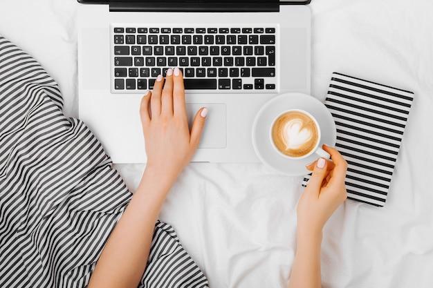 Молодая женщина пьет кофе дома в своей постели и работает на своем ноутбуке, вид сверху