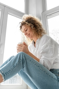 창문 가까이 집에서 커피를 마시는 젊은 여자