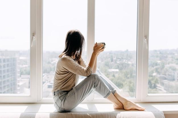 Молодая женщина пьет кофе дома