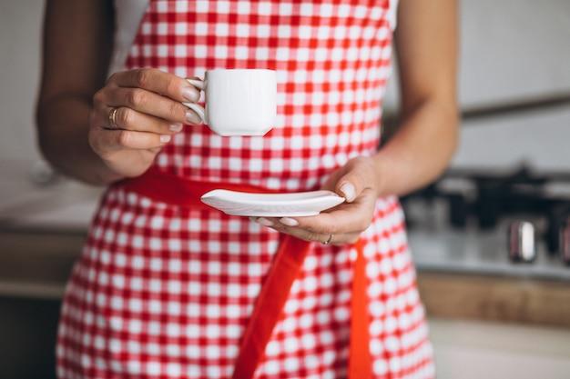 朝のキッチンでコーヒーを飲む若い女性