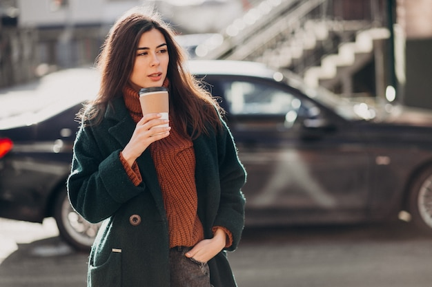 Young woman drinking coffee by her car