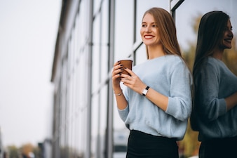 Young woman drinking coffee by the cafe