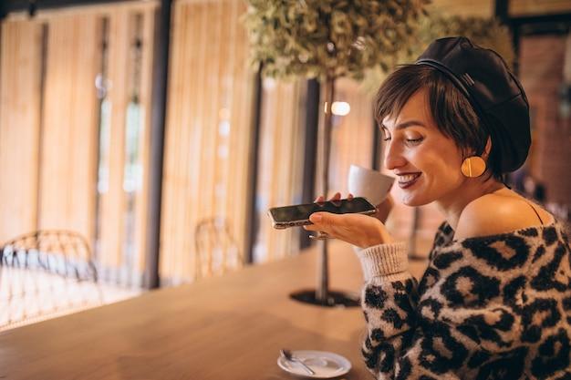 Giovane donna che beve il caffè in un caffè