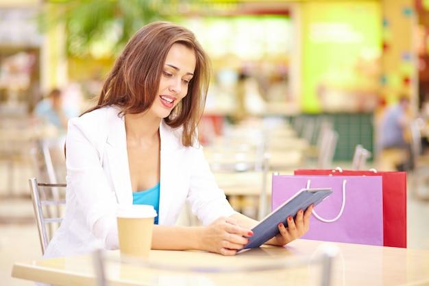 Giovane donna bere caffè e tablet consulenza