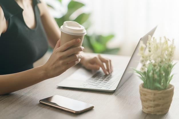Young woman drinking coffee from disposable cup and using computer laptop on work desk.