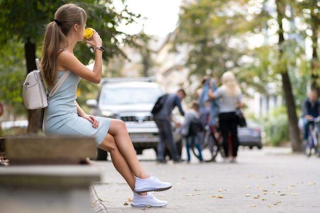 夏の公園の街のベンチに座っている紙コップからコーヒーを飲む若い女性。