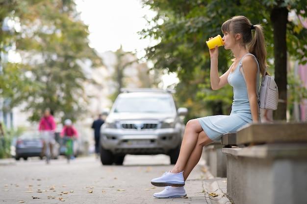 Молодая женщина пьет кофе из бумажного стаканчика, сидя на скамейке на городской улице в летнем парке.