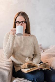 Young woman drinking coffee holding book in hand