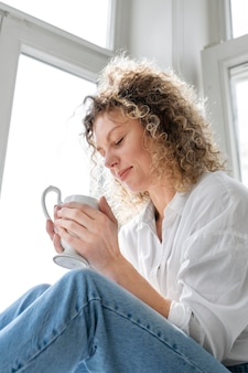 Young woman drinking coffee at home near the window