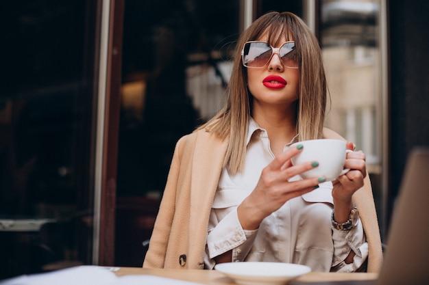 テラスのカフェでコーヒーを飲む若い女性