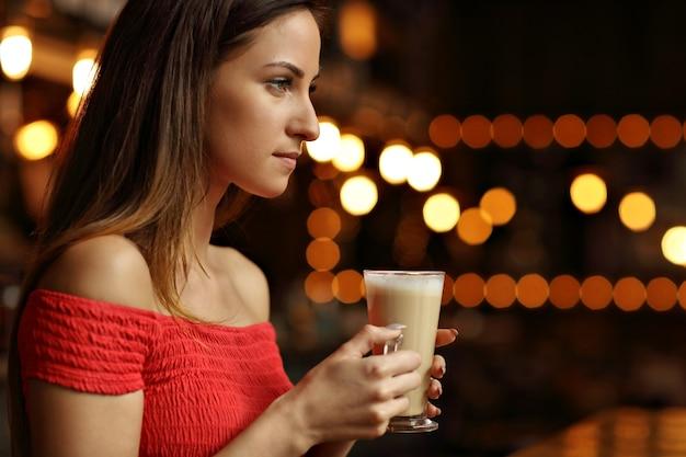 Молодая женщина пьет кофе в кафе