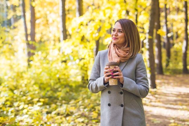 秋の公園でコーヒーを飲む若い女性
