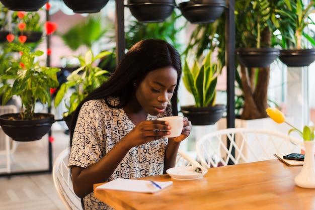 Молодая женщина пьет кофе в современном кафе
