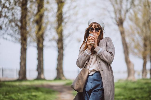 若い女性が公園でコーヒーを飲む