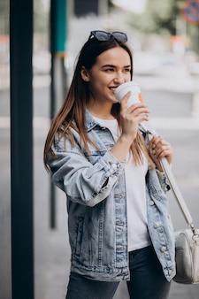 市内でコーヒーを飲む若い女性