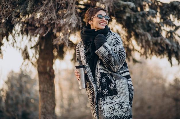 Молодая женщина пьет кофе утром и гуляет в парке